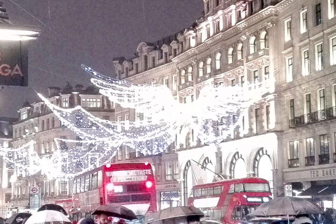 London zu Weihnachten: Doppeldeckerbusse, Weihnachtsbeleuchtung und Menschen mit Regenschirmen in der Regent Street